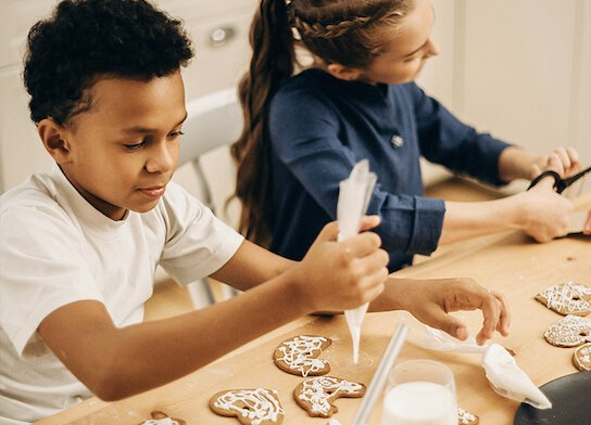 Children icing biscuits at baking class.
